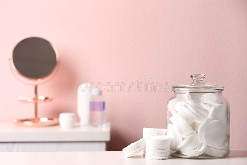 Glass jar with cotton pads on table in bathroom. Space for text stock images