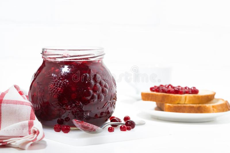 glass jar of cranberry jam on a white table and toasts stock photography