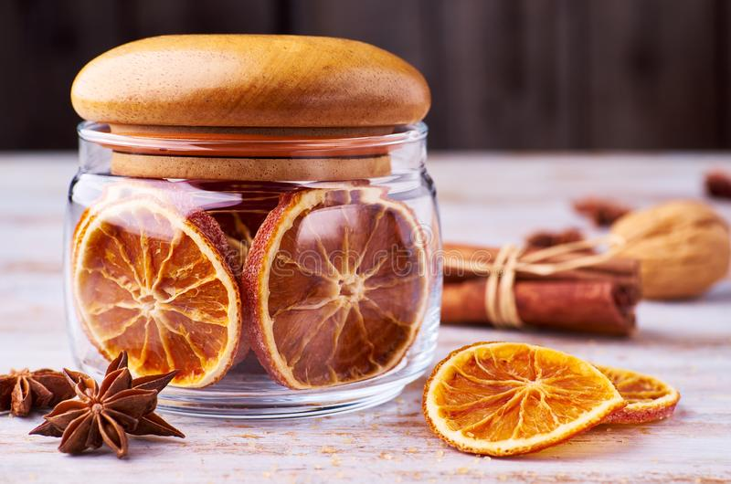 Glass jar with dried oranges and Christmas spices on wooden table royalty free stock photos