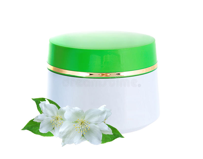 Glass jar of face cream and jasmine flowers stock image