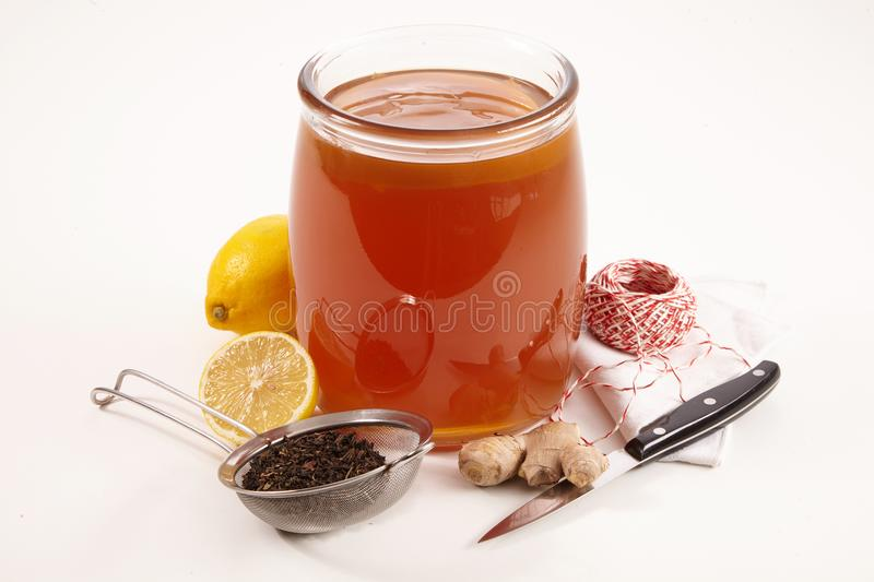 Glass jar of fermented sweetened Kombucha tea. Surrounded with fresh lemon and root ginger for flavoring, tea strainer with leaves, knife and string on white stock image