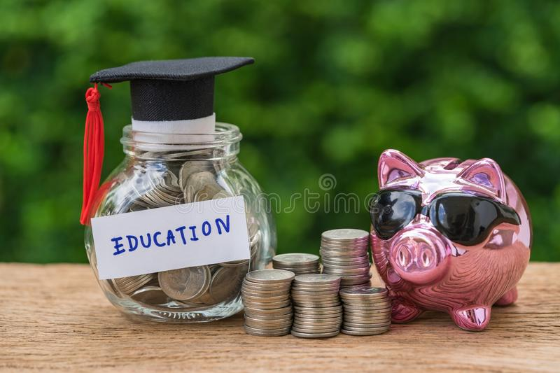 Glass jar with full of coins and graduates hat label with Piggybank and stack of coins as Education, education or savings concept.  royalty free stock image