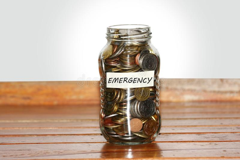A glass jar full of coins to represents emergency. Concept- with masking tape and emergency written on it stock images