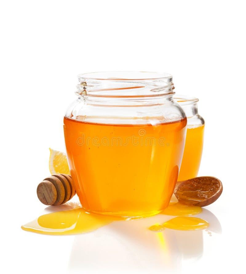 Glass jar full of honey and dipper royalty free stock image