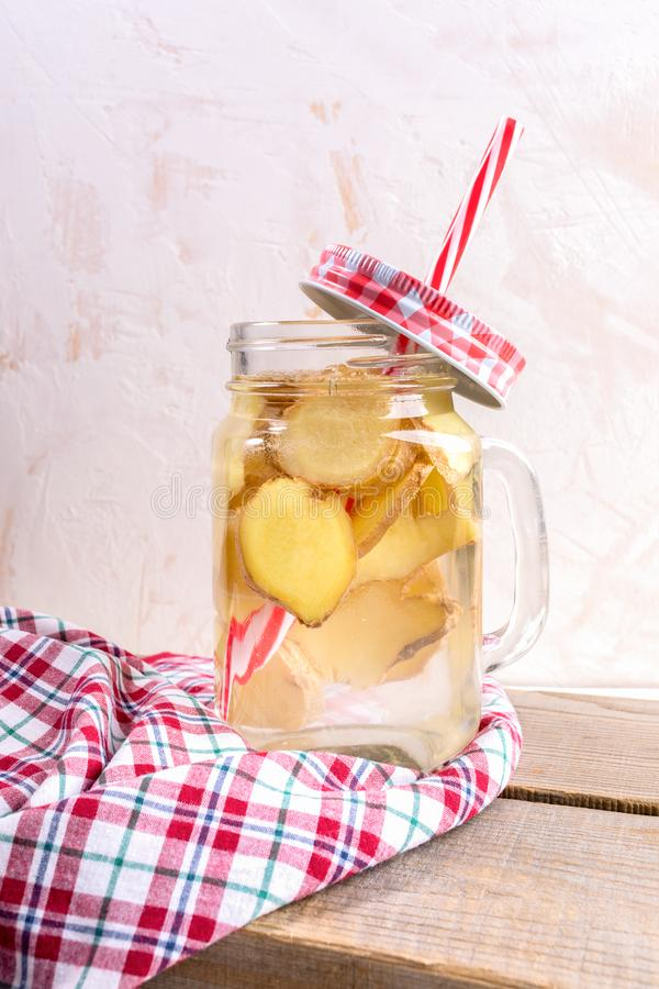 Glass jar with ginger water with straw and red tartan cap on red checkered cloth on wooden planks on light background. Glass jar with ginger water with drinking royalty free stock image