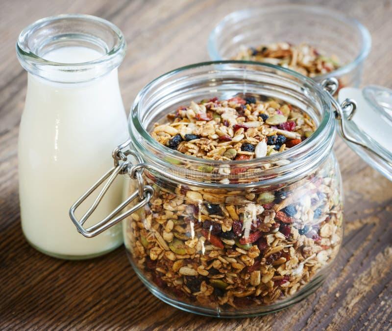 Glass jar of granola and milk stock photos