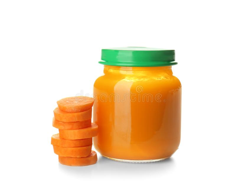 Glass jar with healthy baby food and sliced carrot on white background stock photography