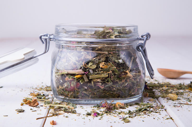 Glass jar with herbal tea on light background royalty free stock photo