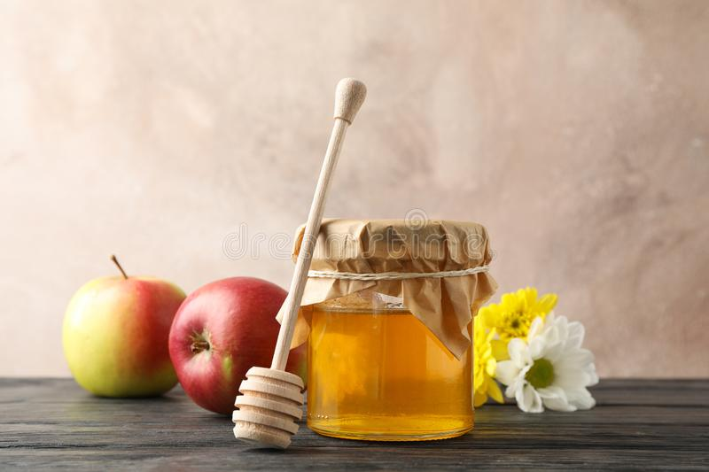 Glass jar with honey, dipper, apples and flowers on wooden background royalty free stock photos
