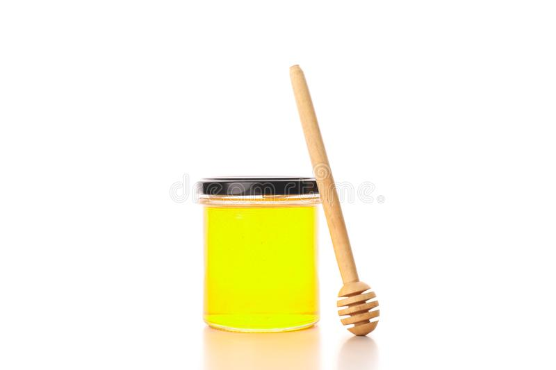 Glass jar with honey and dipper isolated on white royalty free stock photos
