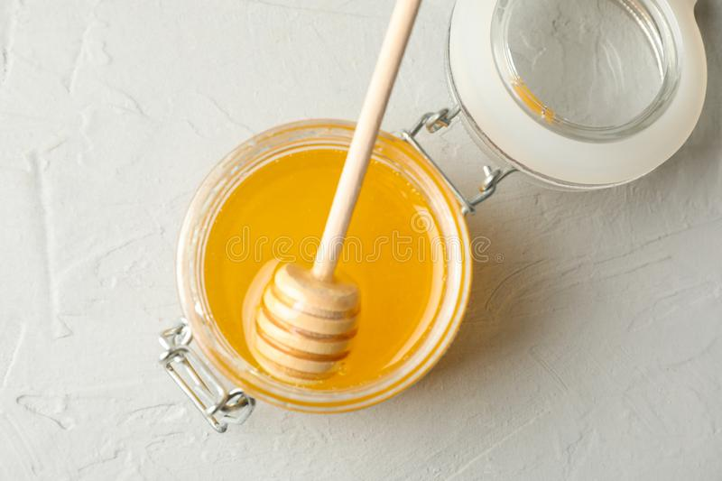 Glass jar with honey and dipper on white background stock image