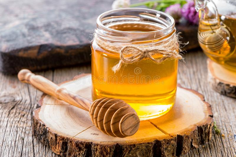 Glass jar of honey with honey dipper on wooden slice close-up stock photography