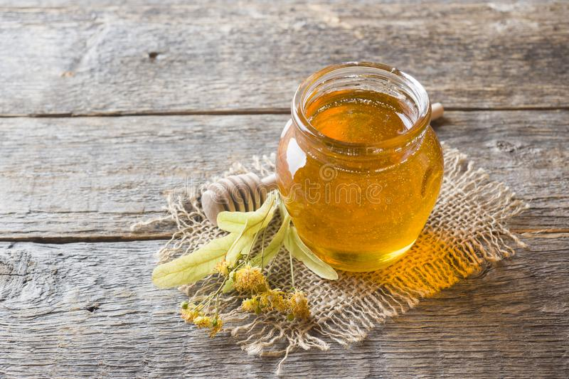 Glass jar of honey, Linden flowers on wooden background royalty free stock image