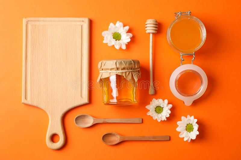 Glass jar with honey and wooden cutlery on color background royalty free stock images