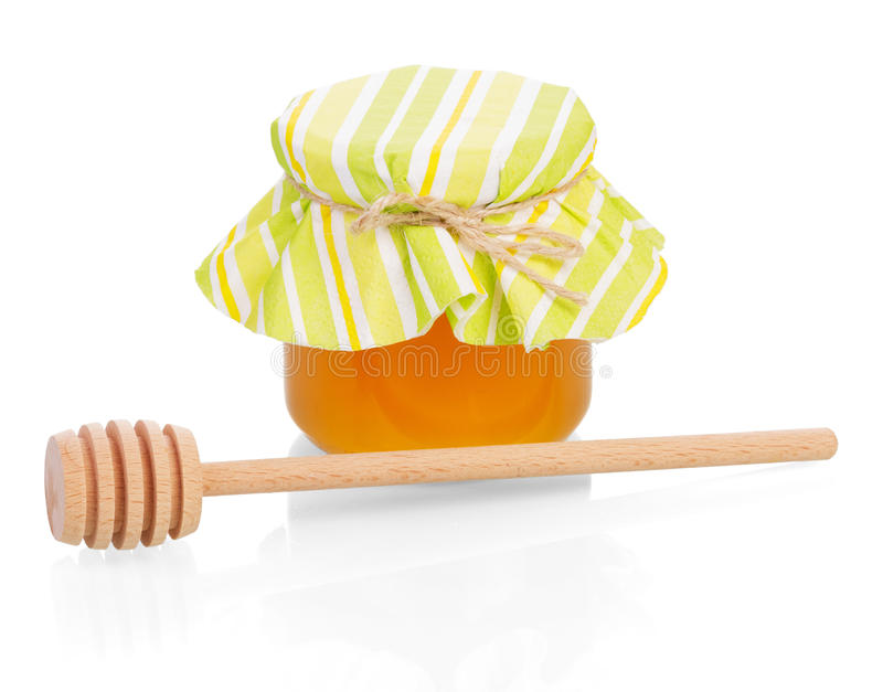 Glass jar with honey and wooden dipper isolated on white. royalty free stock photos