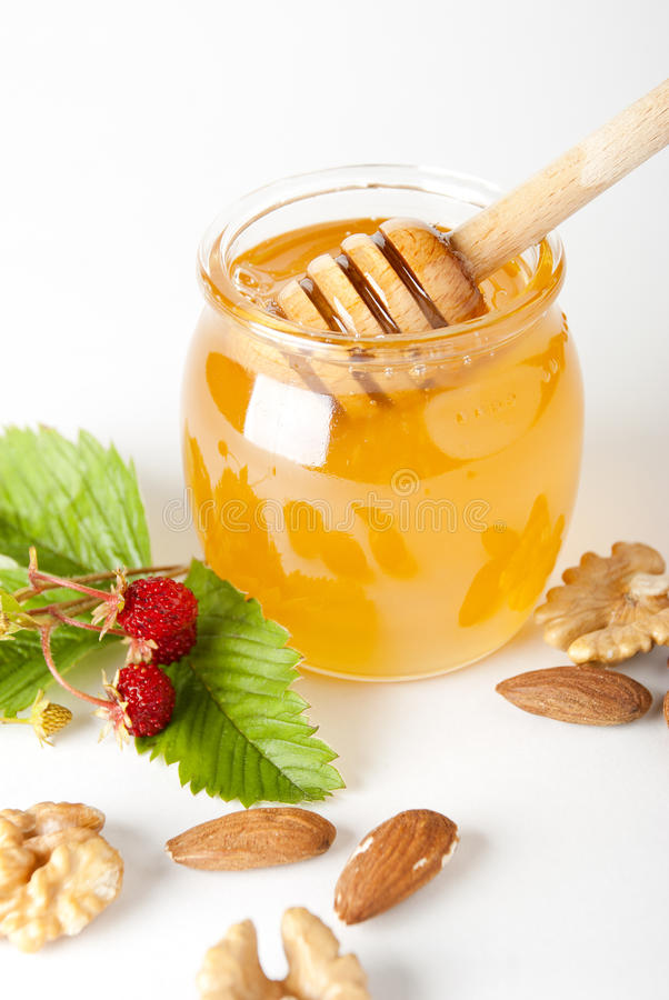 Glass jar of honey with wooden drizzler royalty free stock photos