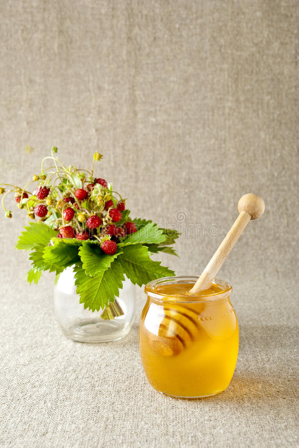Glass jar of honey with wooden drizzler royalty free stock images