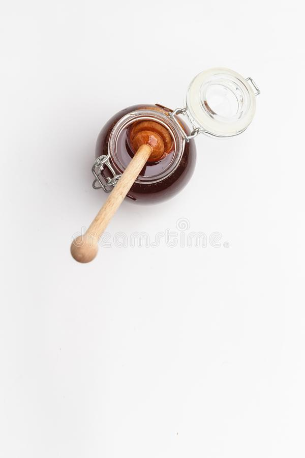 Glass jar with honey and wooden spoon on a white background. Top view. Copy space royalty free stock photo