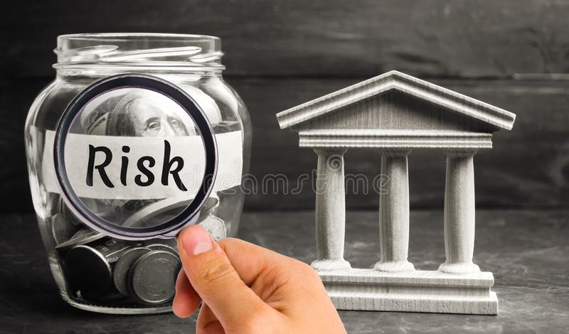 A glass jar and the inscription `risk` stands next to a state building. The concept of financial and economic risk. Unreliable inv stock image