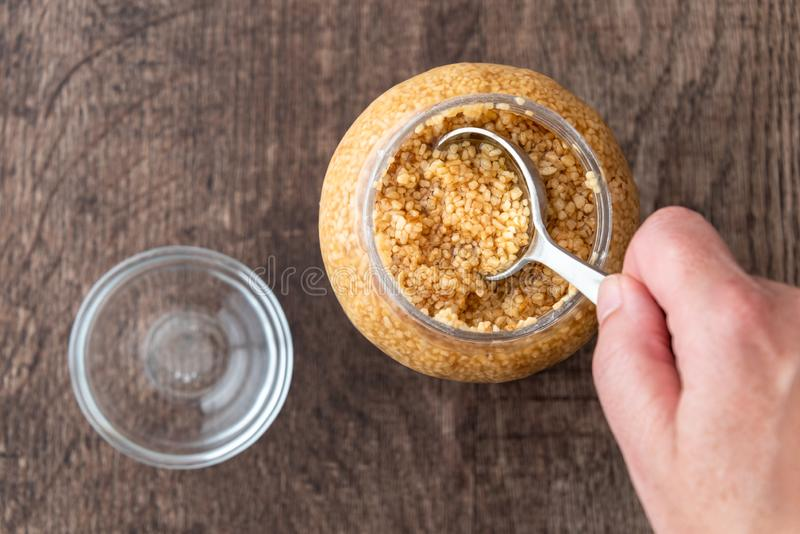 Glass jar of minced garlic and small glass bowl on wood background, woman's hand using tablespoon to scoop out garlic royalty free stock photo