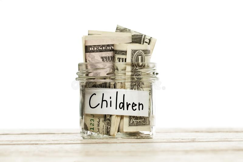 Glass jar with money for children on wooden table against white background.  stock photo