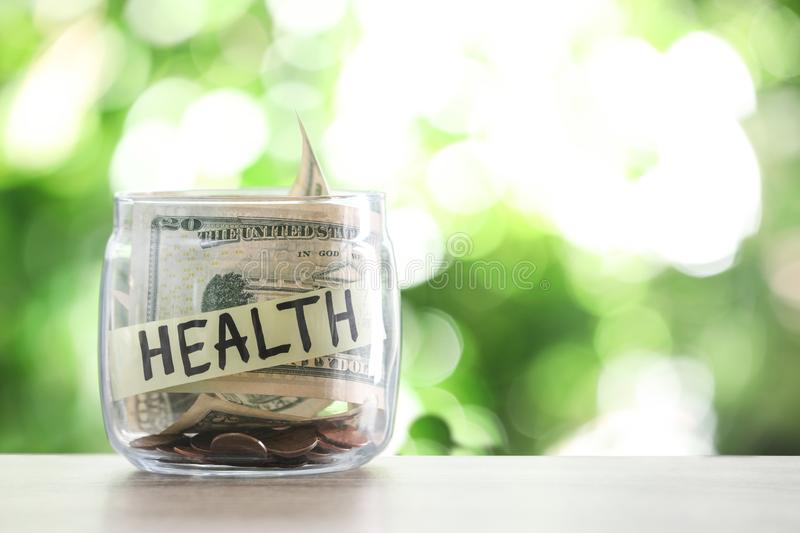 Glass jar with money and label HEALTH on table against blurred background. Space for text royalty free stock photography