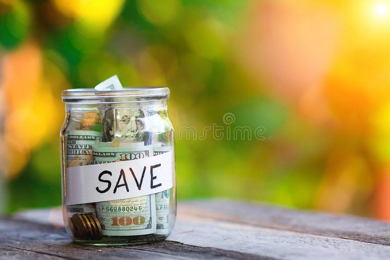 Glass jar with money and label save on table against blurred background. Space for text royalty free stock photo