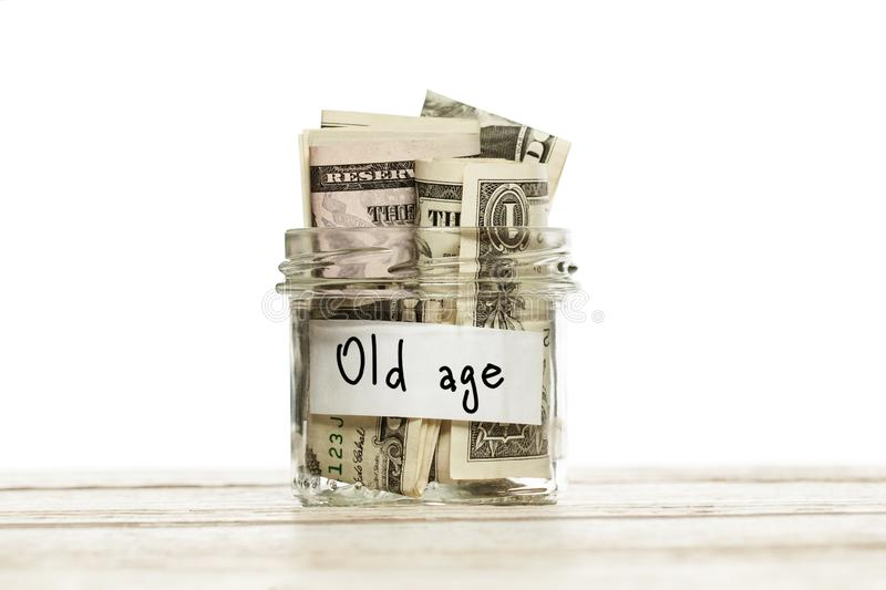 Glass jar with money for old age on wooden table against white background.  royalty free stock photos
