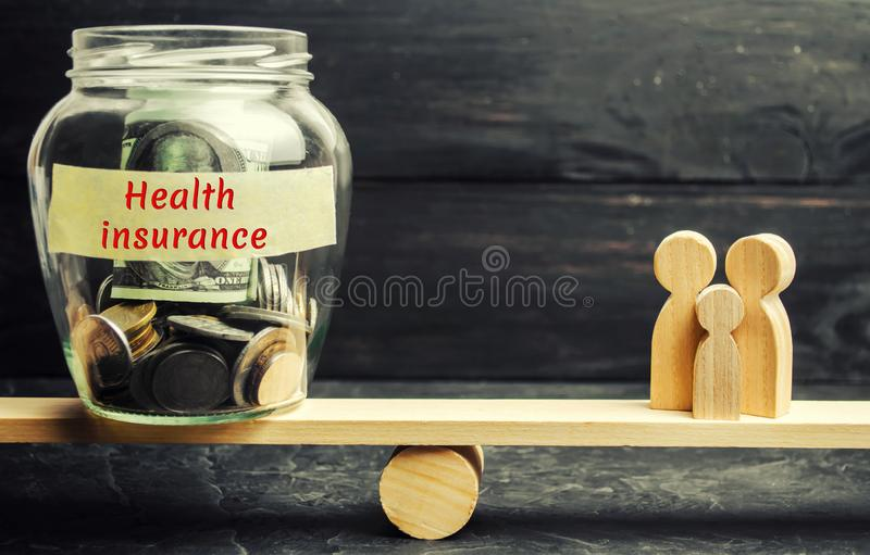Glass jar with money and the words `Health Insurance` and the family on the scales. The concept of medical insurance of life, fami royalty free stock image