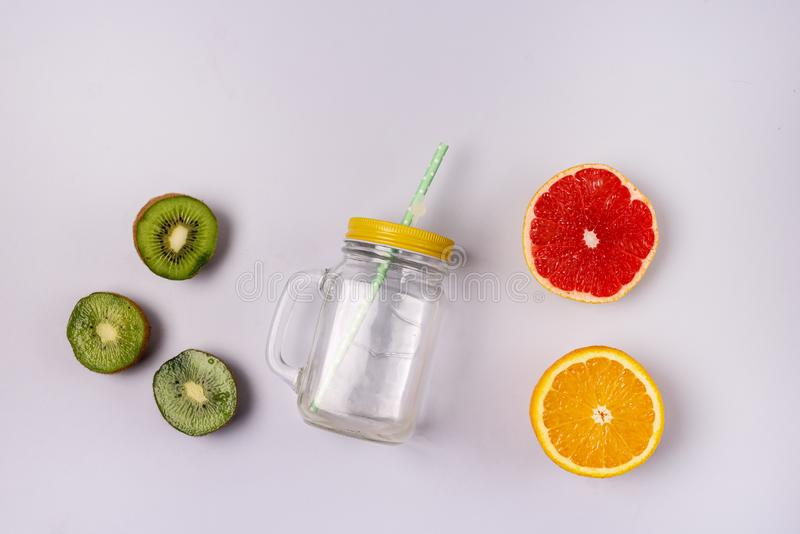 Glass Jar Mug Słoma na niebieskim tle Detox lub Diet Concept Kiwi Orange Grapefruits Składnik dla Smoothie lub Juice Top View fotografia royalty free