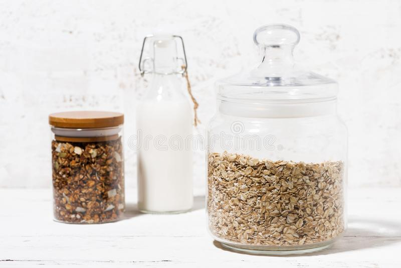 Glass jar with oat flakes, granola and bottle of milk, closeup. Horizontal stock photos