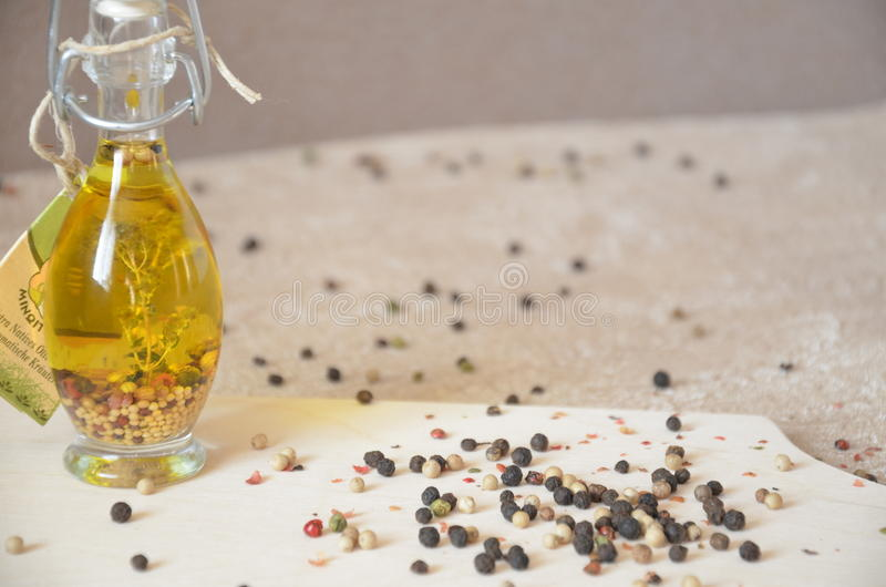 A glass jar with olive oil and spices and sprinkled with pepper on a table stock photos