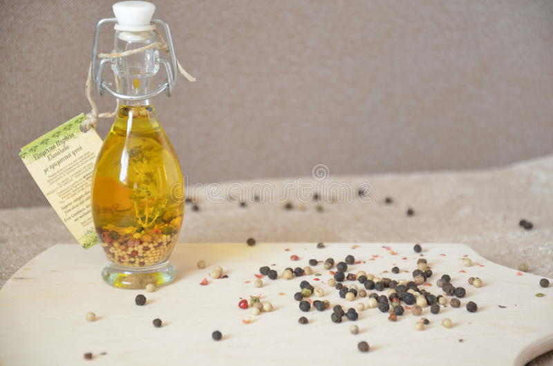 A glass jar with olive oil and spices and sprinkled with pepper on a table royalty free stock images