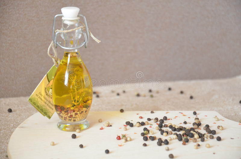 A glass jar with olive oil and spices and sprinkled with pepper on a table royalty free stock photos