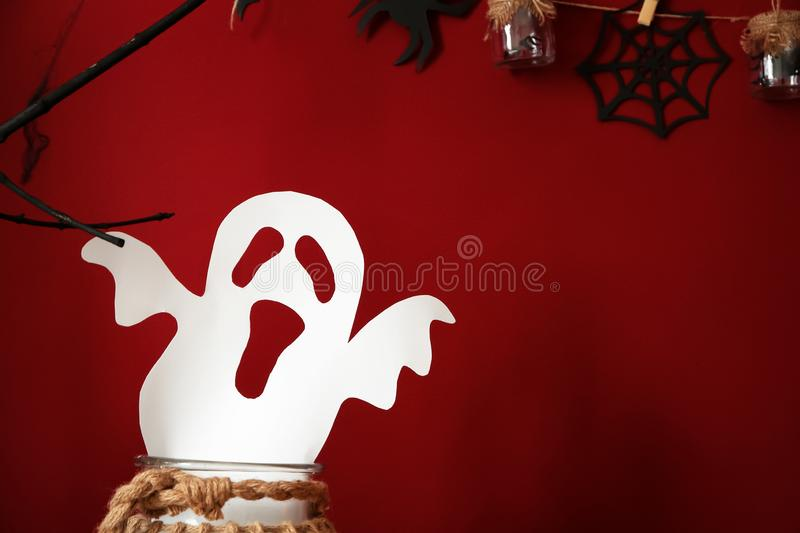 Glass jar with paper ghost for Halloween party on color background stock photos