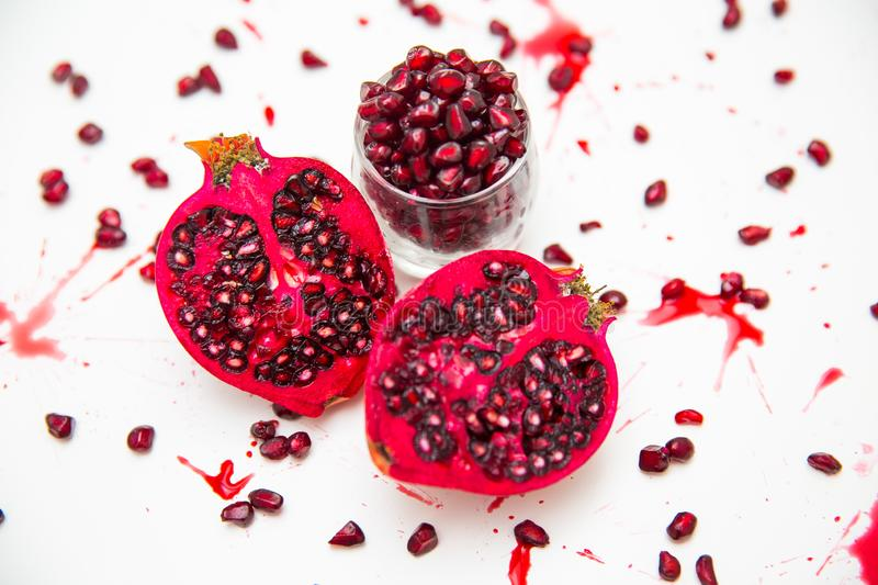 Glass jar with pomegranate seeds, sliced pomegranates and scattered seeds royalty free stock image