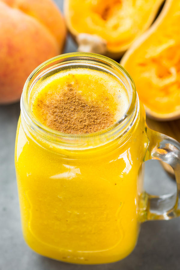 Glass jar with raw vegan pumpkin butternut squash smoothie with peaches, bananas, pie spices. Ingredients on dark stone background. Healthy autumn drink royalty free stock photography
