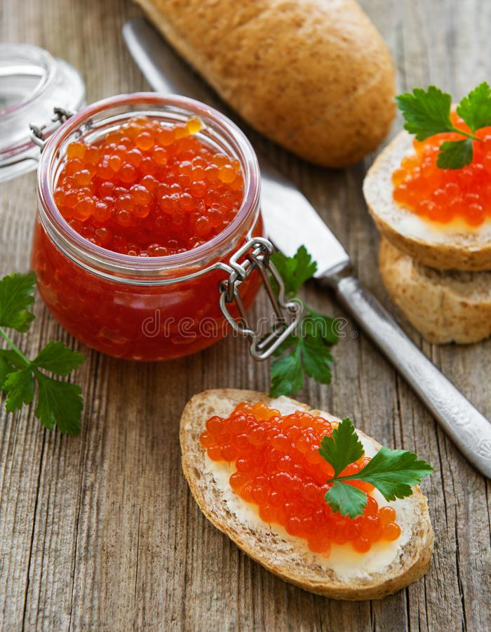 Glass jar of red caviar royalty free stock photo