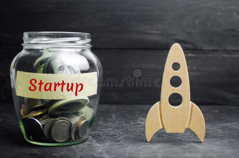 Glass jar, rocket and the word `Startup`. The concept of raising funds for a startup. Charitable contributions to translate ideas. Or project. Business ideas royalty free stock photos