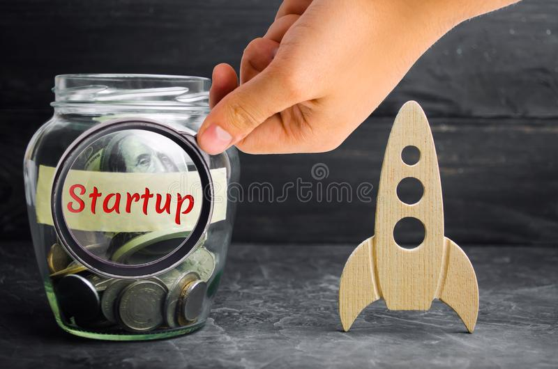 Glass jar, rocket and the word `Startup`. The concept of raising funds for a startup. Charitable contributions to translate ideas. Or project. Business ideas stock image