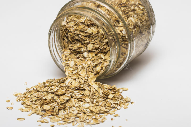 Glass jar with rolled oats isolated on white background royalty free stock images