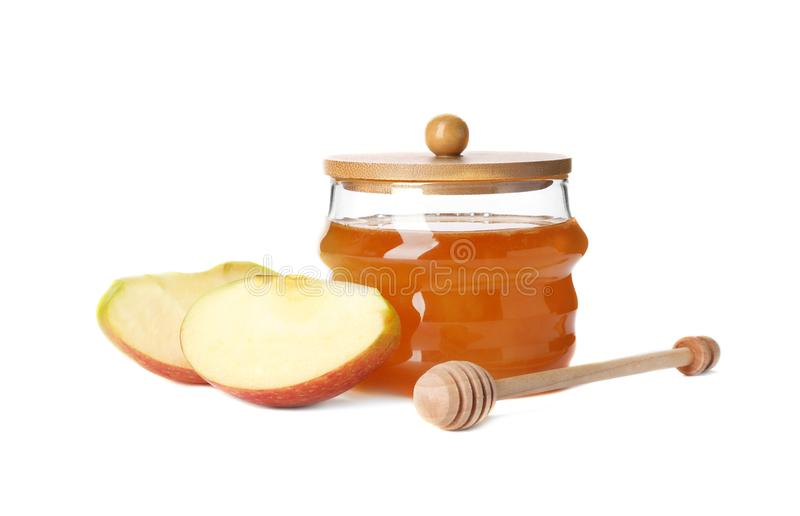 Glass jar with sweet honey and apple. On white background royalty free stock photography