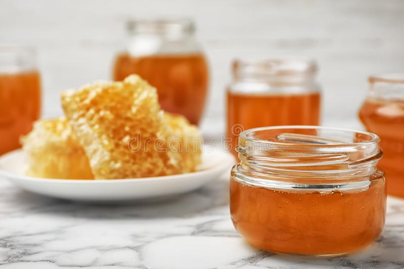 Glass jar with sweet honey. On marble table royalty free stock photos