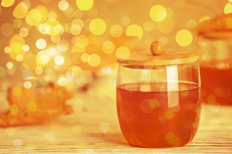 Glass jar with sweet honey on table against  blurred lights stock images