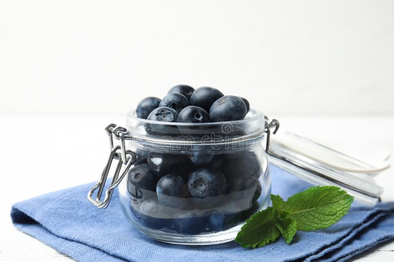 Glass jar of tasty fresh blueberries, mint leaves and fabric on table. Glass jar of tasty fresh blueberries, mint leaves and fabric on white wooden table stock photography