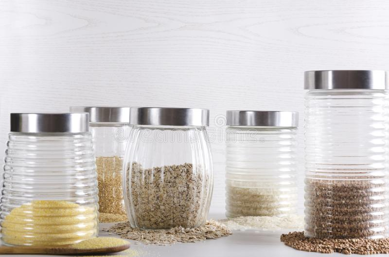 Glass jar and uncooked cereals in it. Healthy and organic cereals in the kitchen royalty free stock image