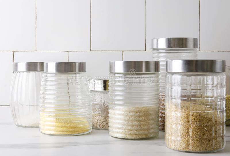 Glass jar with various typies of cereals on the kitchen table stock photos