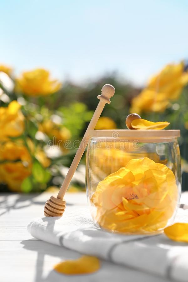 Glass jar with yellow rose and honey dipper on white wooden table in garden stock photos
