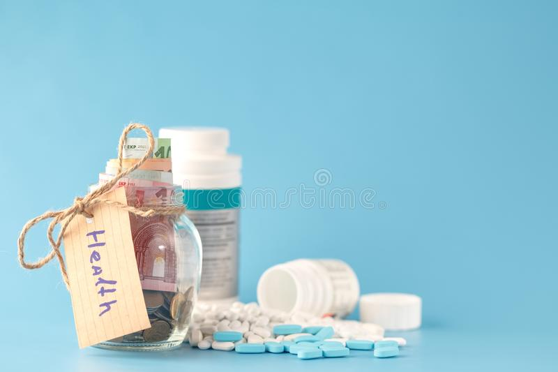Glass jars with coins and `health` text royalty free stock photo