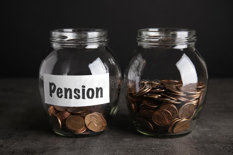 Glass jars with coins and label PENSION on dark stock images